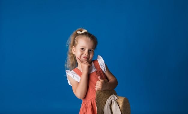밀짚 모자와 쾌활한 작은 금발 소녀는 공간의 복사본과 함께 파란색 표면에 선다