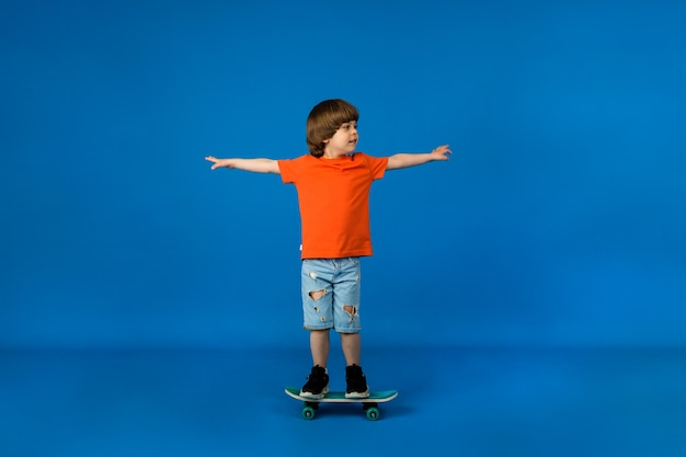 Playful little boy with brown hair rides a skateboard on a blue surface with a place for text