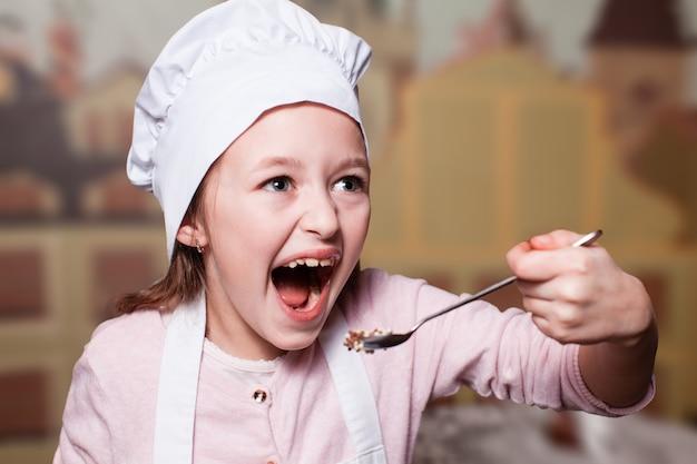 요리사 모자를 쓴 장난기 많은 어린 소녀가 초콜릿으로 가득 찬 숟가락을 핥습니다.