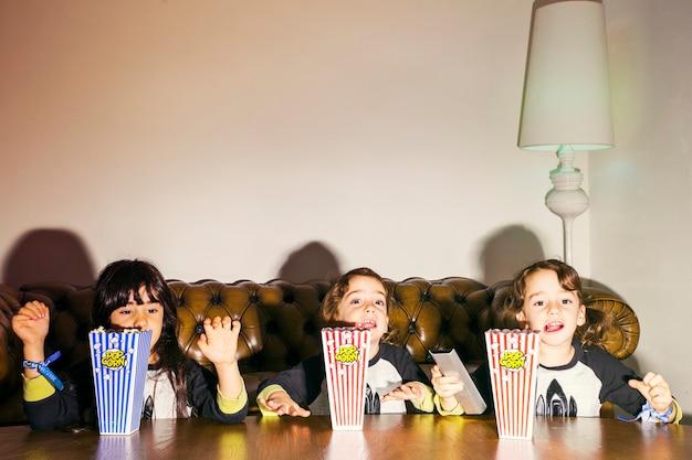 Playful little girls with popcorn in dark