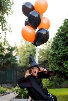 Игривый маленький мальчик в карнавальном костюме волшебника угрожает празднованию хэллоуина на заднем дворе