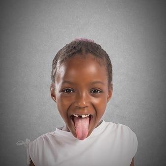遊び心のある小さなかわいい女の子が舌を作る