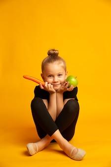당근과 녹색 사과를 손에 들고 다이어트와 건강한 식생활 개념을 들고 노란색 배경에 검은색 운동복과 뽀인트 신발을 신은 장난기 많은 작은 스포츠우먼