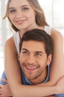 장난기 많은 사랑의 커플. 그녀의 남자 친구를 포옹 하 고 카메라에 웃는 아름 다운 젊은 여자