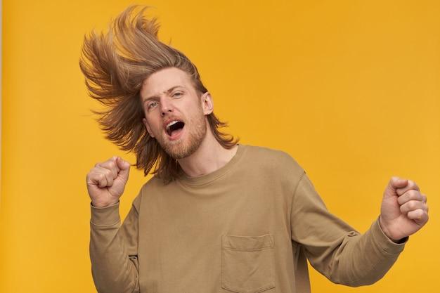 Игривый мужчина, красивый бородатый парень со светлой прической. в бежевом свитере. танцы и машут головой. не сдерживается. изолированные над желтой стеной