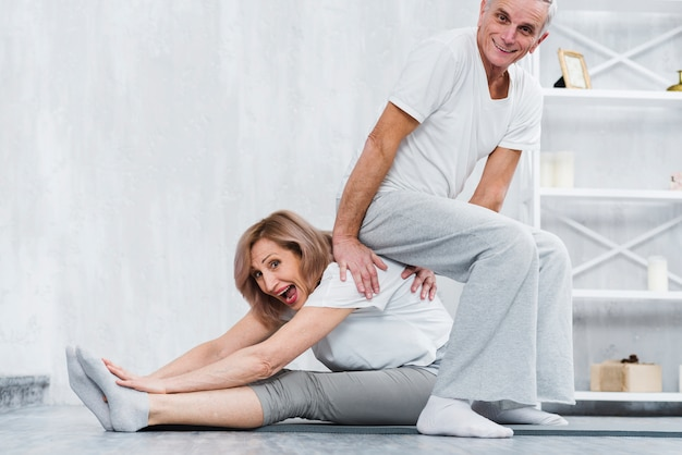 Playful man sitting on back of his wife while doing yoga at home