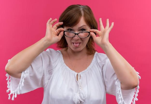 안경을 쓰고 안경에 손을 얹고 고립 된 분홍색 벽에 혀를 보여주는 장난이 심한 중년 여성