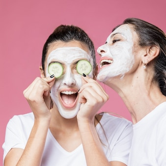 Playful mom and daughter with face mask