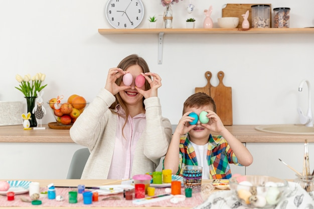 Playful mom and son covering eyes with painted eggs