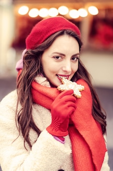 쾌활한 분위기. 쿠키를 먹는 동안 그녀의 얼굴에 미소를 유지하는 매력적인 여성 사람