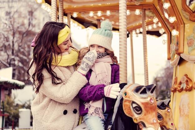 쾌활한 분위기. 그녀의 딸을 들으면서 양성을 표현하는 매력적인 여자