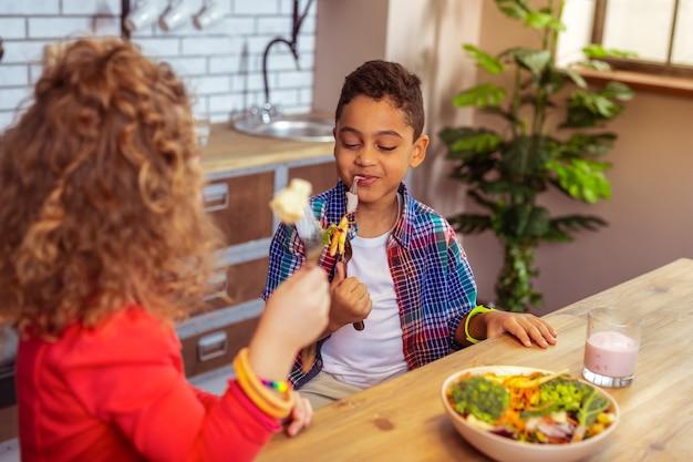 Игривое настроение. довольный мальчик-брюнетка, выражающий позитив, поедая овощи