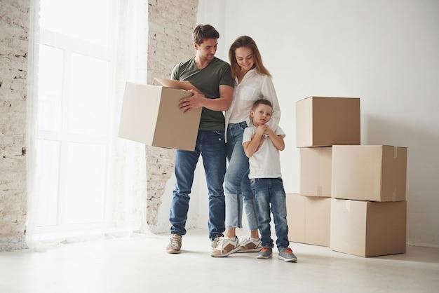 아이의 장난기 넘치는 분위기. 가족이 새 집으로 이사했습니다. 움직이는 상자 포장 풀기.