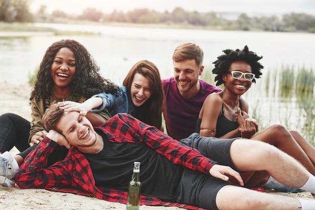 Игривое настроение. группа людей устраивает пикник на пляже. друзья веселятся в выходные.