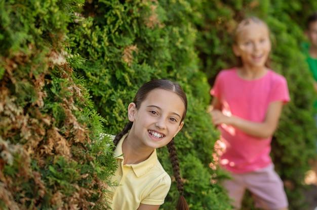 장난스러운 분위기. 따뜻한 날에 공원에 있는 키 큰 녹색 덤불 밖을 즐겁게 바라보는 땋은 머리와 여자 친구를 가진 즐거운 소녀