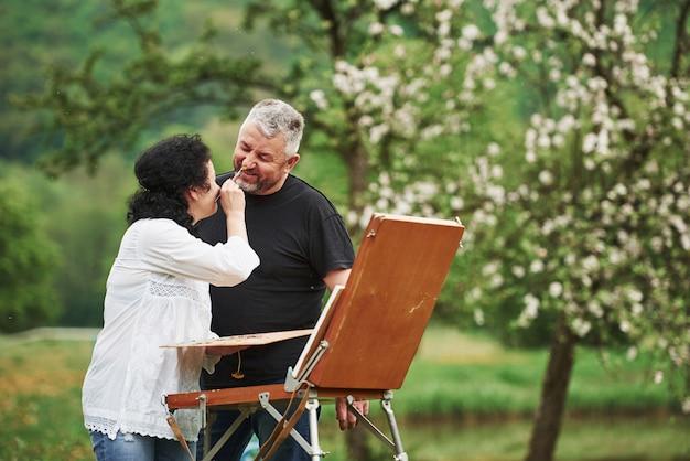 Игривое настроение. пожилая пара отдыхает и вместе работает над краской в парке