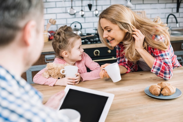 Playful mother and daughter looking at each other holding coffee cup