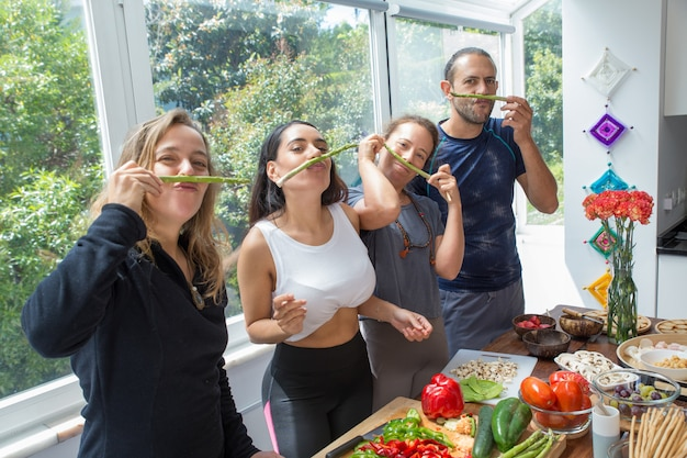 Playful people making fake moustache from asparagus