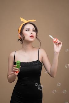 黄色の背景の上にパーティーの泡を吹く遊び心のあるピンナップ女性