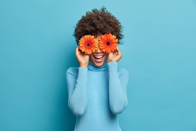 Playful positive african american woman covers eyes with two orange gerberas, enjoys spring time, fresh flowers, has fun, dressed casually,