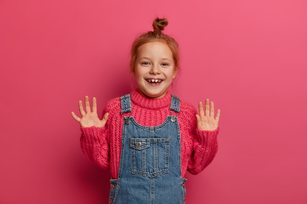 Playful positive girl with ginger hair combed in bun, raises palms and has good mood, poses for family photo in , wears knitted sweater and sarafan, has joyful expression isolated over rosy wall