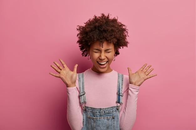 La giovane donna afroamericana positiva e giocosa alza i palmi delle mani, impazzisce per ascoltare notizie incredibili, ride, vestita con dolcevita e sarafan, posa sul muro rosa. concetto di emozioni felici