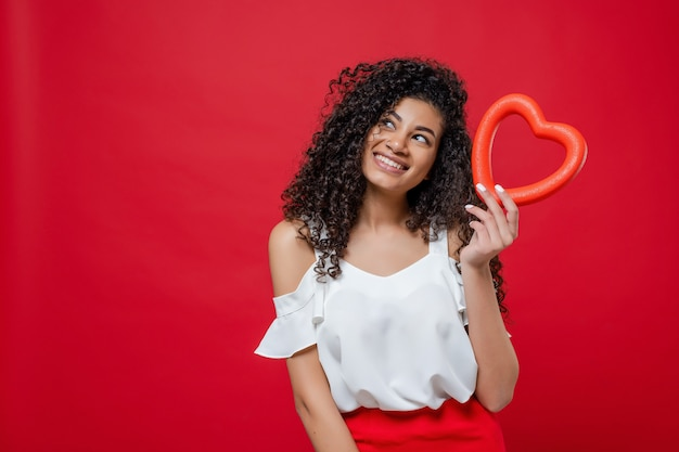 Playful pretty black woman with curly hair holding heart shape and looking at copyspace isolated on red
