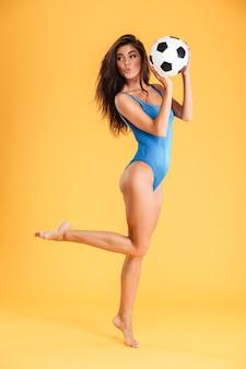 오렌지 벽에 고립 된 한쪽 다리에 포즈를 취하는 파란색 수영복에 쾌활한 꽤 스포티 한 웃는 젊은 여자