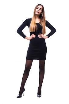 Donna graziosa giocosa in piedi in abito nero su bianco in tutto il corpo