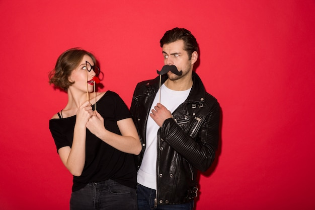 Playful punk couple posing with fake mustache, lips and eyeglasses