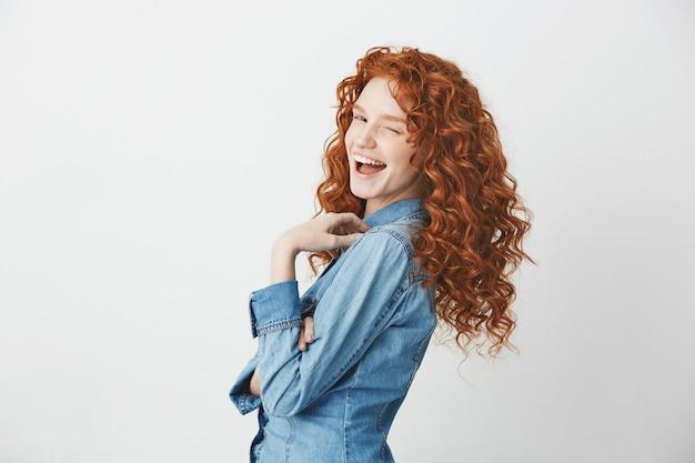 Игривая рыжая девушка улыбается, подмигивая стоя в профиле.