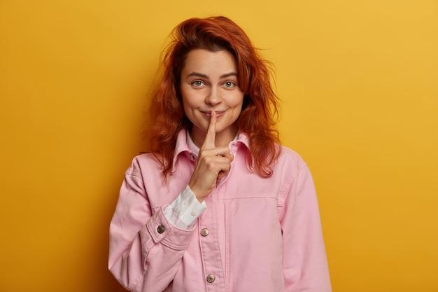 Donna graziosa giocosa rossa con sguardo segreto soddisfatto, fa un gesto di silenzio, pettegolezzi con un amico, vestito con una giacca di jeans roseo