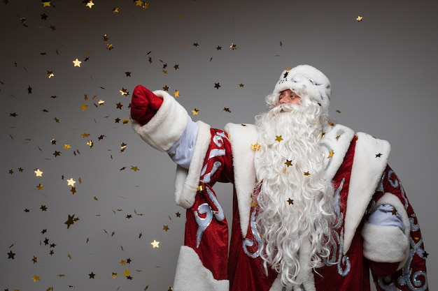 Playful santa claus catching golden stars shaped confetti on gray studio background
