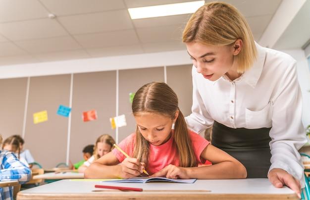 教師やクラスメートと一緒に学校の時間とレッスンを楽しんでいる遊び心のある学校の生徒