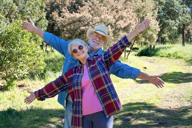 두 팔을 뻗은 숲에서 장난 수석 부부는 자유를 즐기는 은퇴