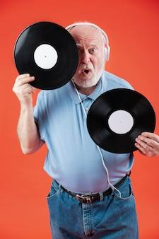 Playful senior holding music records