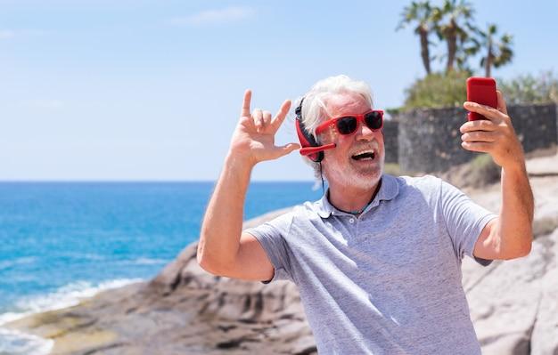 Игривый старший мужчина выражает счастье и радость, стоя у моря в видеозвонке с мобильным телефоном