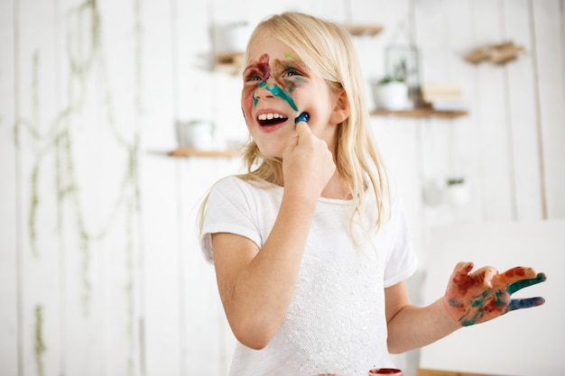 ペンキの指で彼女の顔に触れる遊び心のある7歳のブロンドの女の子。少女は顔をさまざまな色で描いた。子供の遊び。