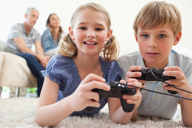 Playful siblings playing video games with their parents on the b