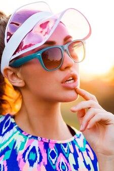 Игривая стройная девушка в стильном красочном укороченном топе, прозрачной кепке и солнцезащитных очках позирует на улице на закате.