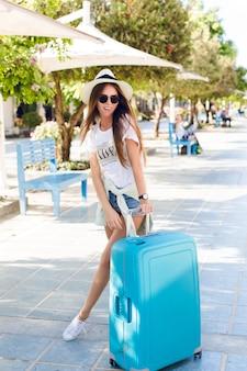 青いスーツケースの公園で立っている遊び心のあるスリムな若い女の子。彼女はデニムのショートパンツ、白いtシャツ、麦わら帽子、濃いサングラス、白いスニーカーを着ています。彼女は笑顔で足を組んでいます