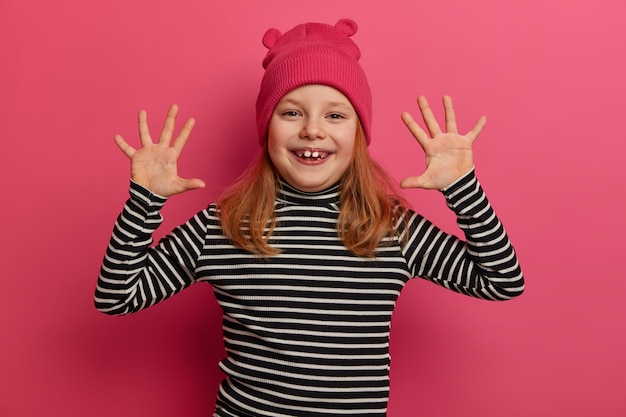 Playful small cute girl raises palms, feels happiness, wears funny hat with ears and striped jumper, smiles broadly, shows white baby teeth, plays with friends, isolated over bright pink wall