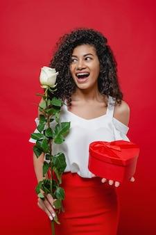 遊び心のある笑顔の黒人女性が保持している白いバラと赤に分離されたハート形のギフトボックス