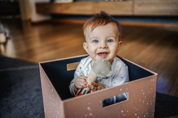 Игривый улыбающийся кавказский очаровательный маленький белокурый мальчик сидит в коробке и играет со своей любимой игрушкой. домашний интерьер.