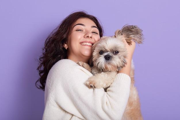 Игривая улыбающаяся самка обнимает маленькую собачку-пекинес, веселится вместе, дружеские отношения, темноволосая дама смотрит позитивно, стоит у фиолетовой стены.