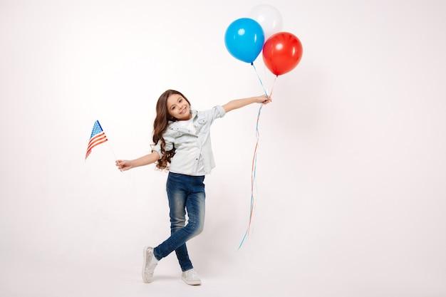 Игривый улыбающийся маленький ребенок, держащий американский флаг и воздушные шары, выражая радость и стоя изолированным в белой стене