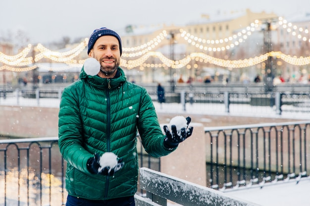 Playful smiling male juggles with snowballs throws them in air, has happy expression