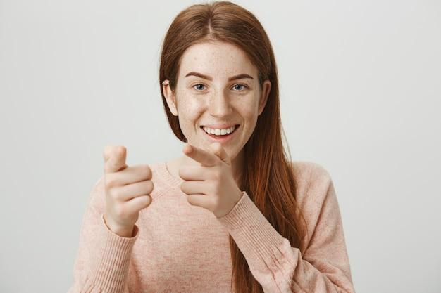 Giocosa sorridente ragazza rossa che punta le dita, congratulazioni