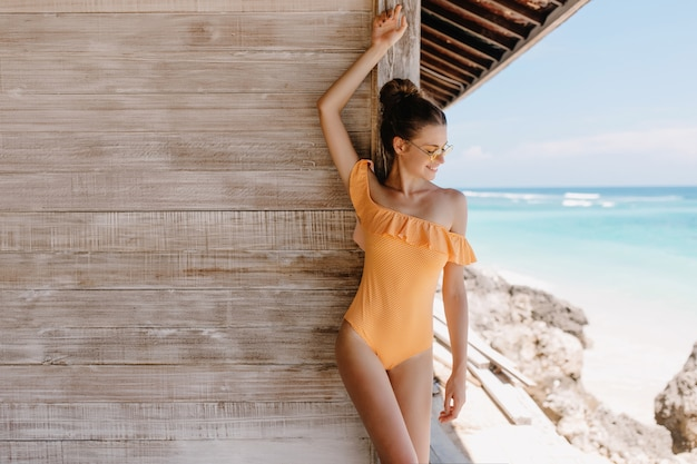Playful tanned girl in orange swimwear standing near wooden house and looking at sea. cute brown-haired woman having fun at exotic resort in her vacation.