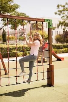 Playful teen schoolgirl on climbing net on playground